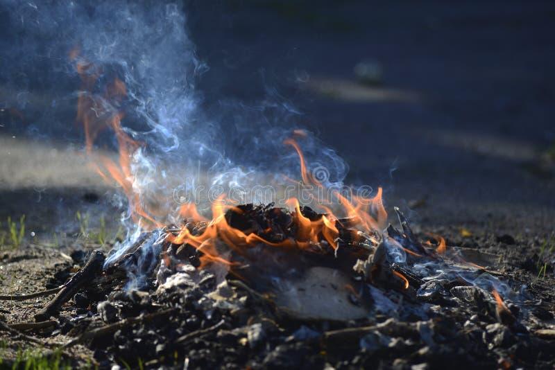 Een kleine brand op het asfalt Verlichting van vuren stock afbeeldingen