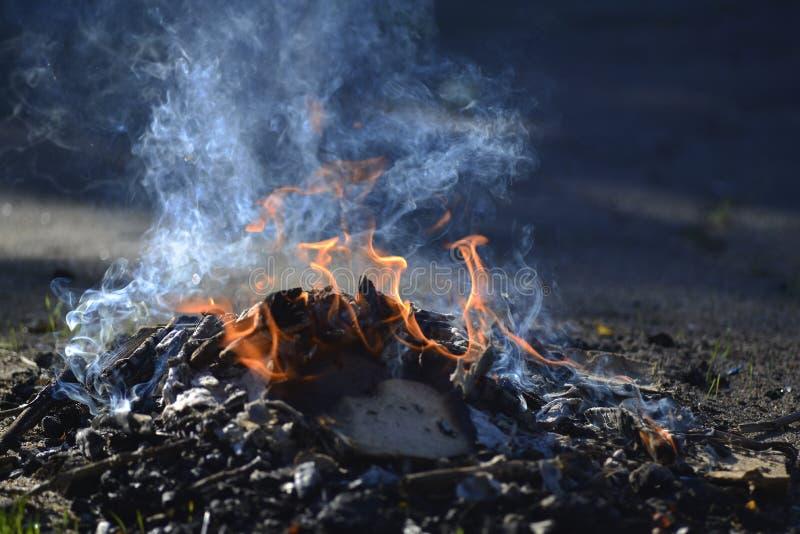 Een kleine brand op het asfalt Verlichting van vuren Rook van de brand royalty-vrije stock foto's