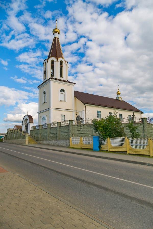 Een kleine die kerk door een hoge omheining tegen een bewolkte blauwe hemel wordt omringd royalty-vrije stock foto's