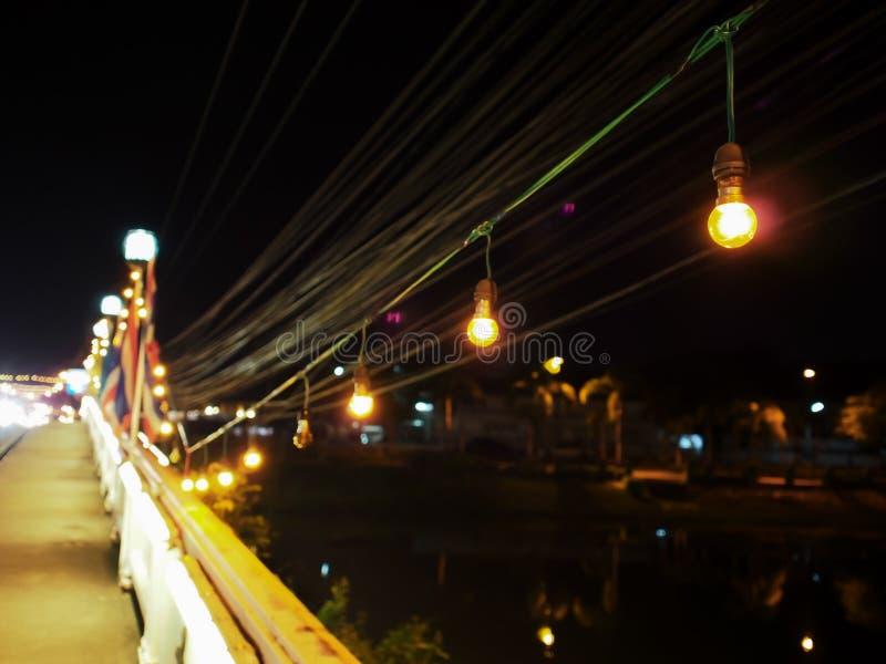 Een kleine gele gloeilamp die op een openbare brug werd verfraaid stock afbeeldingen