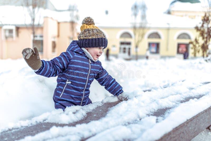 Een kleine gelukkige jongen van 3-6 jaar oude spelen in de winter in de stad, hebbend pret het spelen sneeuwballen, die sneeuw ve royalty-vrije stock afbeelding