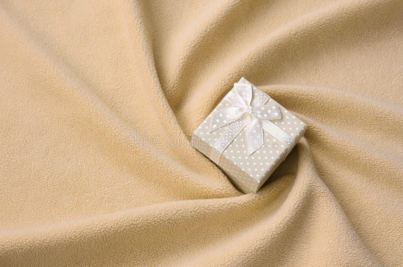 Een kleine giftdoos in sinaasappel met een kleine boog ligt op een deken van zachte en bont lichtoranje vachtstof met heel wat hu stock afbeeldingen