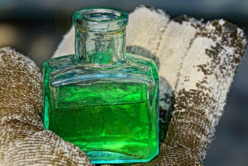 Een kleine glasfles met groene vloeistof bevindt zich op de palm van een gloved hand stock foto's
