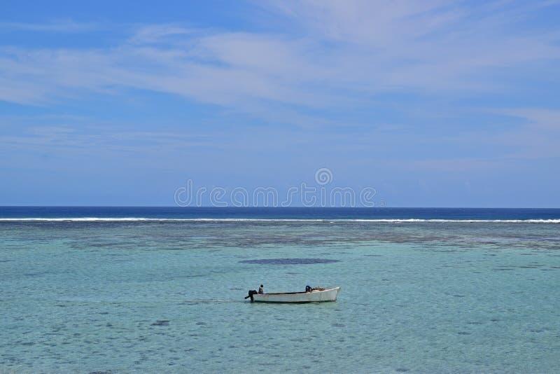 Een kleine houten vissersboot met twee vissers op een seaview met horizon die water en hemel scheidt royalty-vrije stock foto's