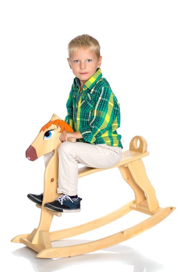 Een kleine jongen berijdt een houten paard stock foto