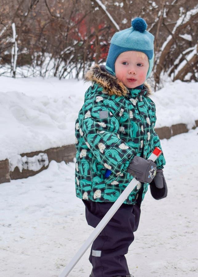 Een kleine jongen bevindt zich met een hockeystok in de winter in een sneeuwpark stock afbeelding