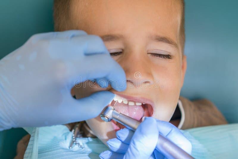 Een kleine jongen bij de ontvangst van een tandarts in een tandkliniek De tandheelkunde van kinderen, Pediatrische Tandheelkunde  royalty-vrije stock foto