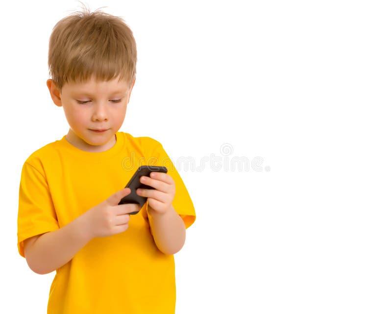 Een kleine jongen communiceert op een mobiele telefoon royalty-vrije stock foto