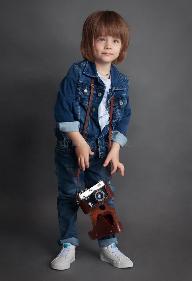 Een kleine jongen in denim en uitstekende camera stock afbeelding