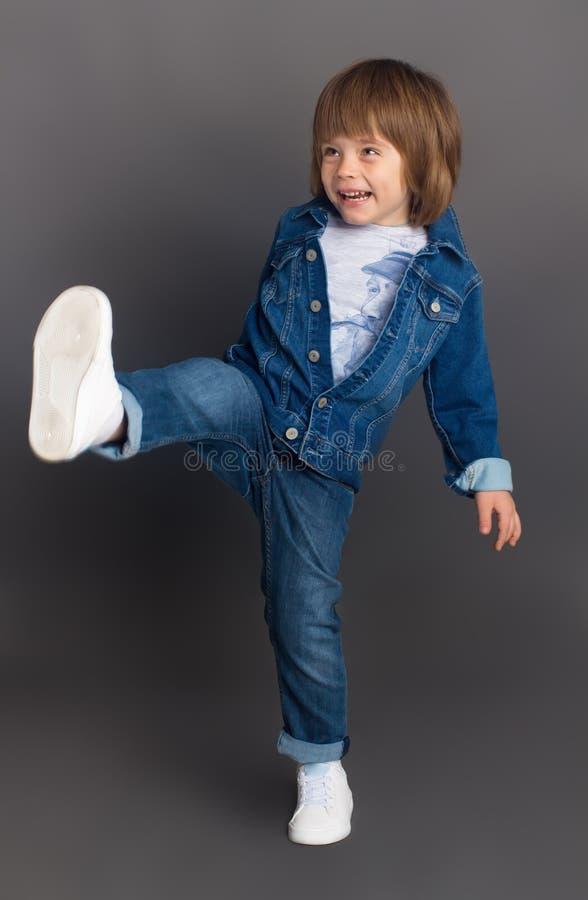 Een kleine jongen in denim lacht en voor de gek houdt rond in de studio royalty-vrije stock foto