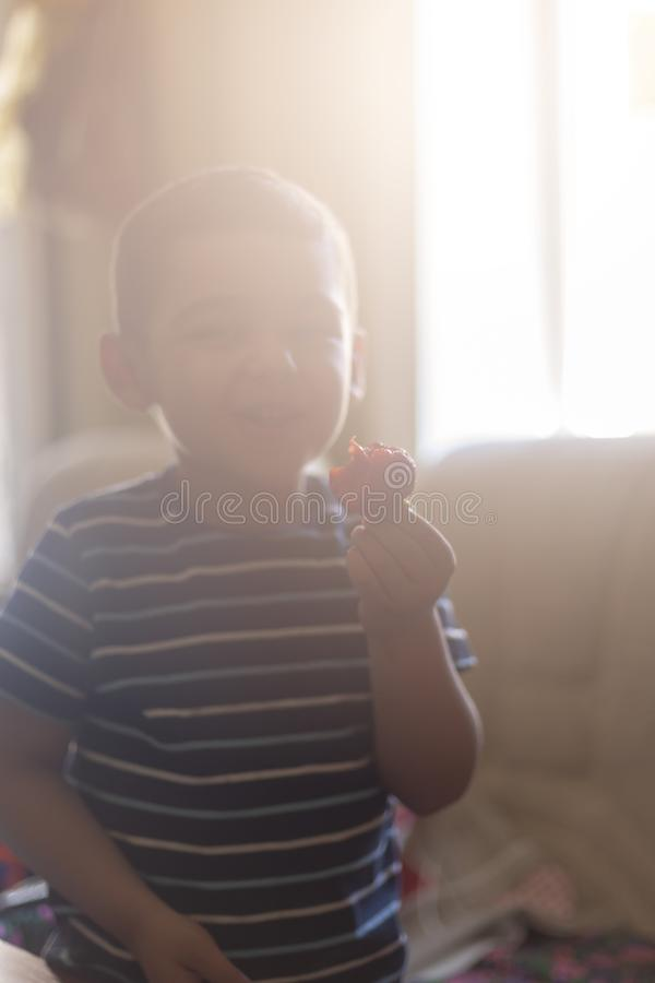 Een kleine jongen die aardbeien eten De zomervoedsel Een jong jong geitje eet een yummy aardbei royalty-vrije stock afbeelding