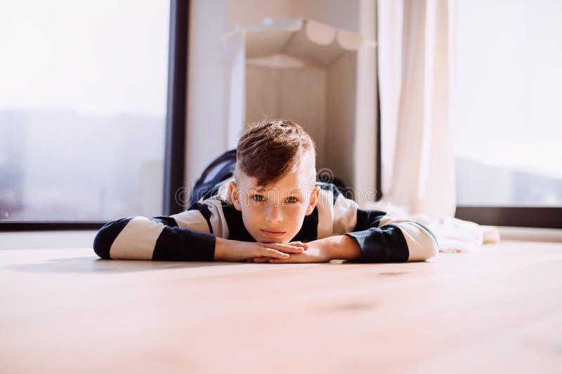 Een kleine jongen die binnen op de vloer thuis liggen De ruimte van het exemplaar stock afbeelding