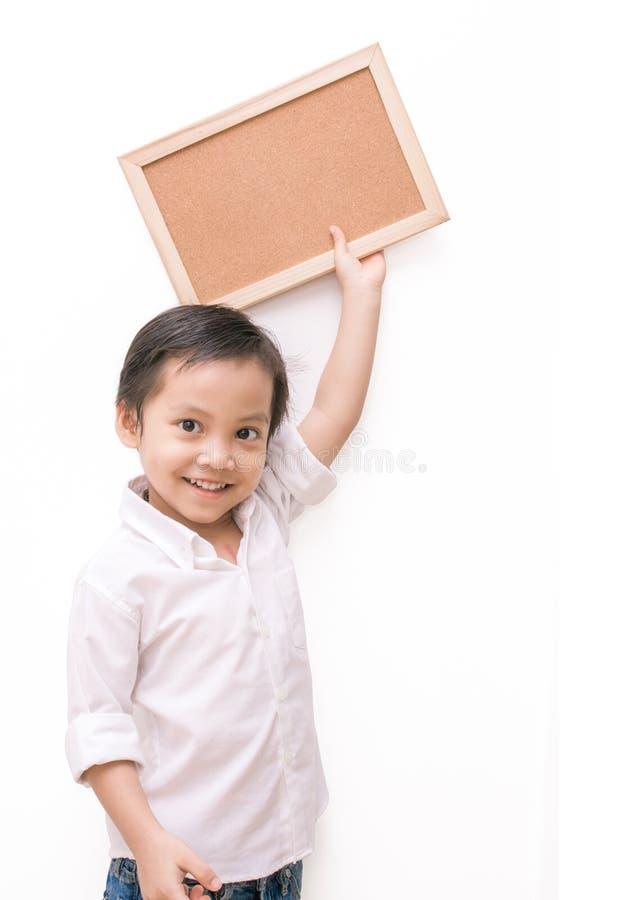 Een kleine jongen die een raad over witte achtergrond houden stock afbeelding