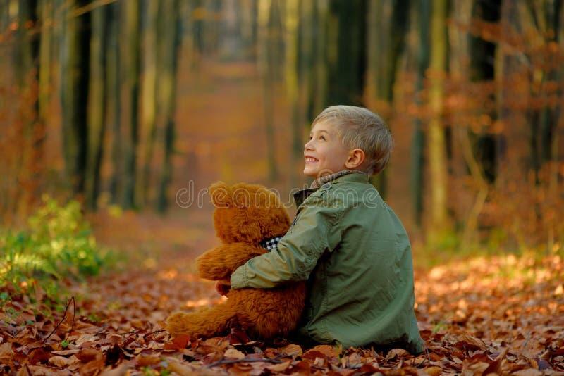 Een kleine jongen die in het de herfstpark spelen stock foto
