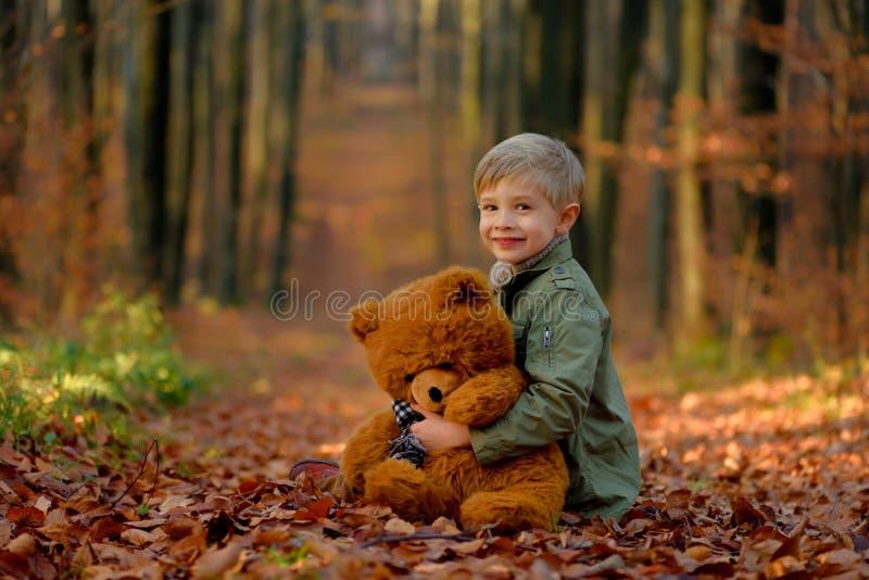 Een kleine jongen die in het de herfstpark spelen stock afbeelding
