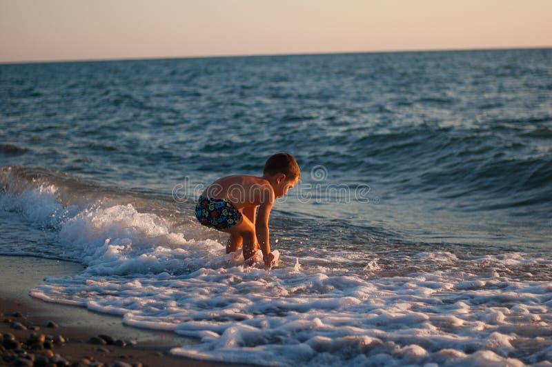 Een kleine jongen die in het zand op de Zwarte Zee in plonsen van golven, bij zonsondergang van de dag spelen Strand Golovinka royalty-vrije stock fotografie
