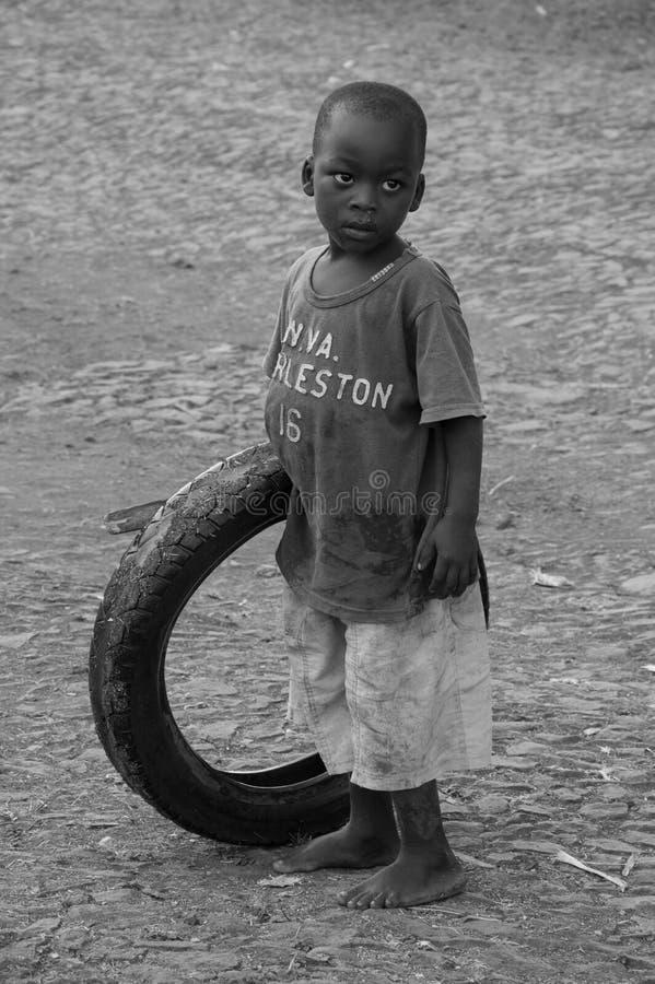 Een kleine jongen die met een gebruikte autobanden spelen in de wegen van Guadalupe stock afbeeldingen