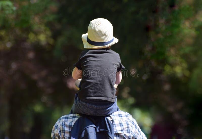 Een kleine jongen die op de schouders van zijn vader berijden royalty-vrije stock afbeeldingen