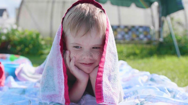 Een kleine jongen die op het gazon op een hete de zomerdag liggen Het kind is pret en actief om hun vrije tijd door te brengen ge royalty-vrije stock afbeelding