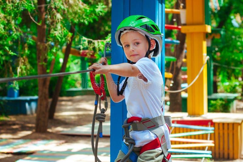 Een kleine jongen die een park van de avonturenkabel onderzoeken stock foto