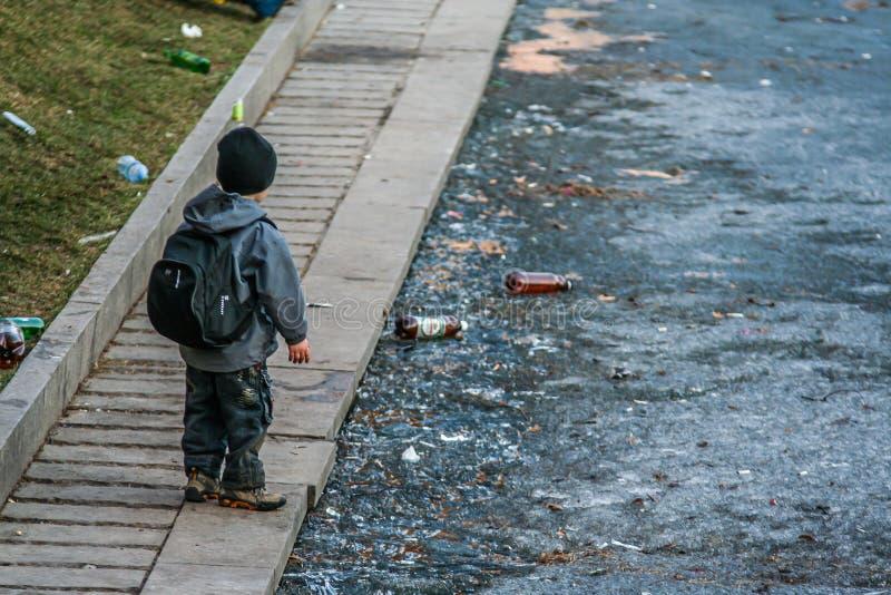 Een kleine jongen die zich door de vijver bevinden die ijs en huisvuil behandelen stock afbeeldingen