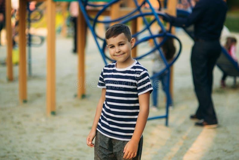 Een kleine jongen in een gestreepte T-shirt speelt op de speelplaats, Schommeling op een schommeling De lente, zonnig weer royalty-vrije stock afbeeldingen
