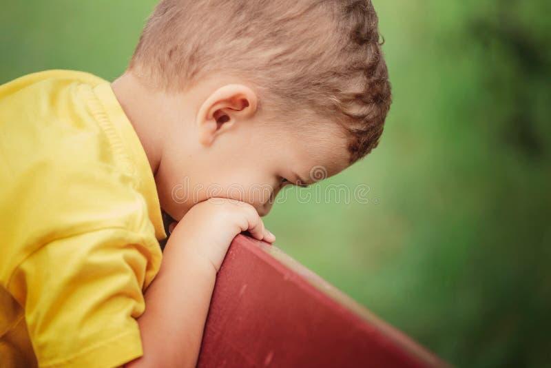 Een kleine jongen in een gele T-shirt zit op een parkbank en droevig Close-up royalty-vrije stock afbeelding