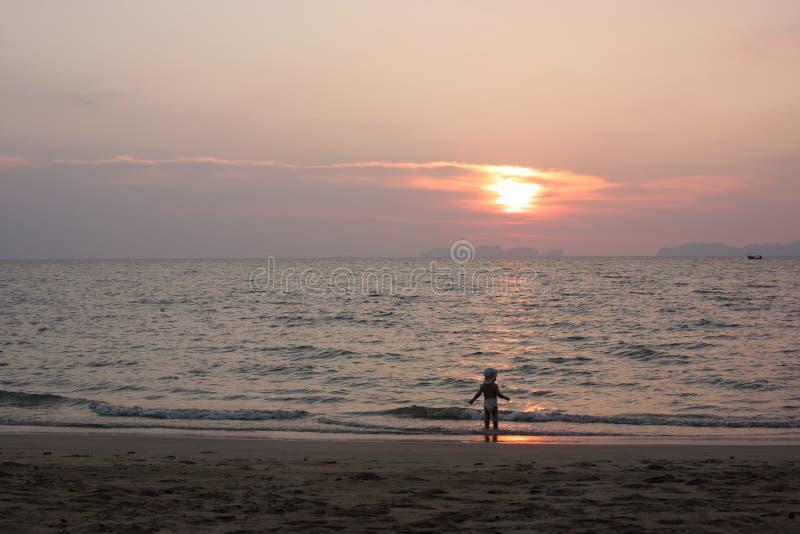 Een kleine jongen geniet van de laatste zonstralen op het strand royalty-vrije stock afbeeldingen