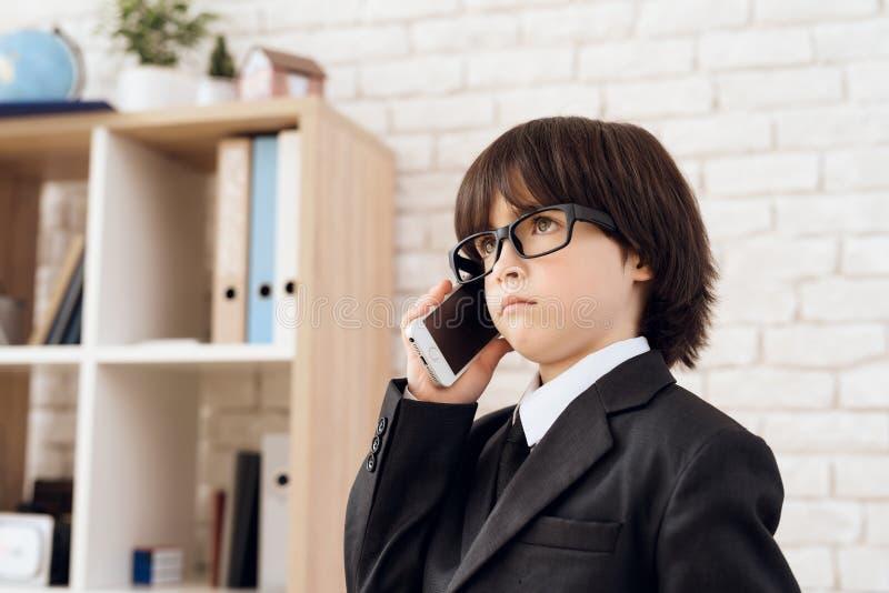 Een kleine jongen in glazen en kostuum stelt zich als zakenman voor De donker-haired jongen speelt een rijke man royalty-vrije stock foto