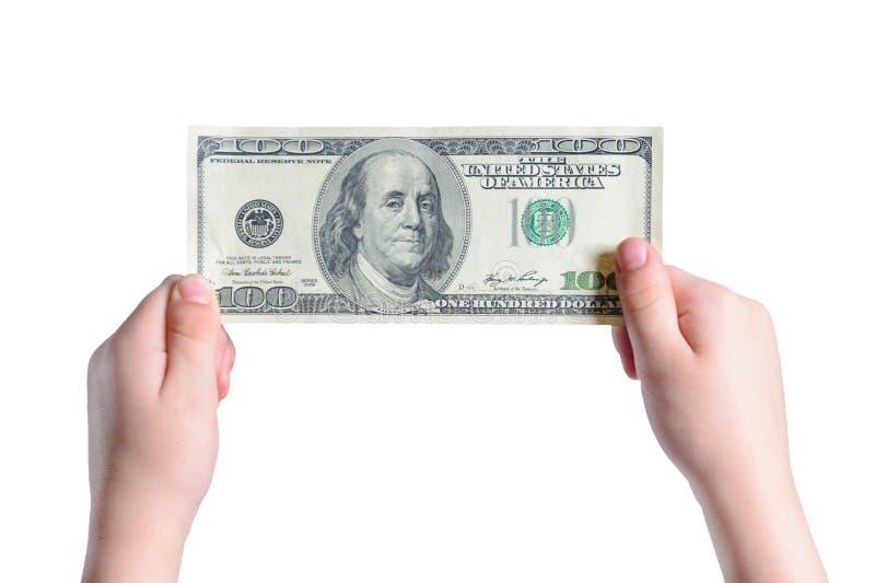 Een kleine jongen houdt 100 dollars in zijn die handen, op een witte achtergrond worden geïsoleerd royalty-vrije stock foto