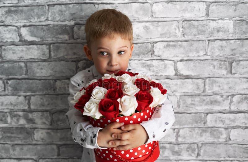 Een kleine jongen houdt een grote rode doos met rode en witte rozen stock foto's