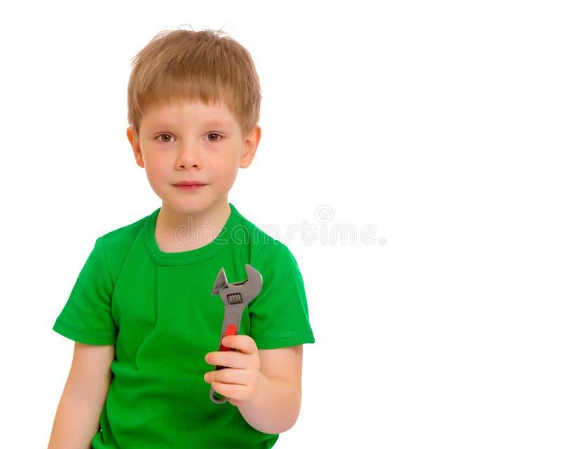 Een kleine jongen houdt een moersleutel in zijn hand royalty-vrije stock foto's