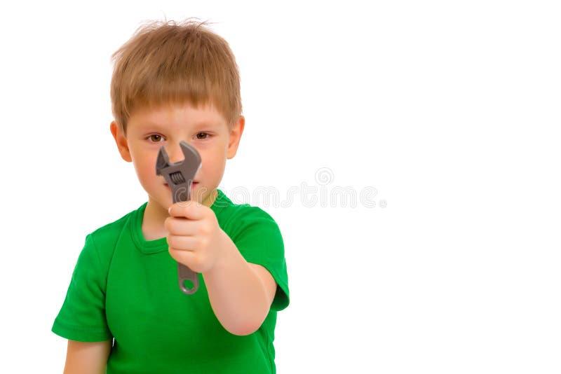 Een kleine jongen houdt een moersleutel in zijn hand stock fotografie