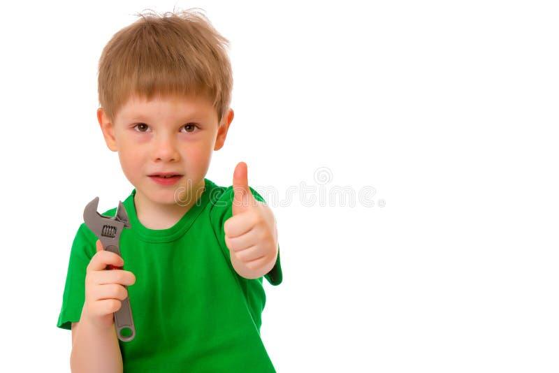 Een kleine jongen houdt een moersleutel in zijn hand stock foto's