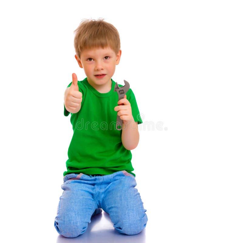 Een kleine jongen houdt een moersleutel in zijn hand royalty-vrije stock afbeeldingen
