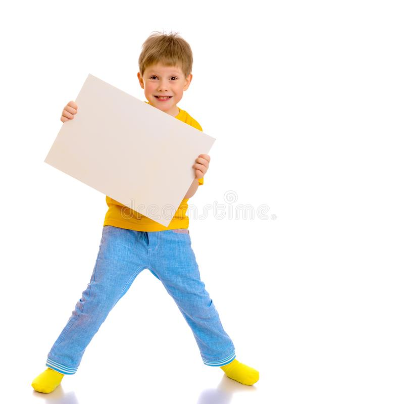 Een kleine jongen kijkt van achter een lege banner stock afbeelding