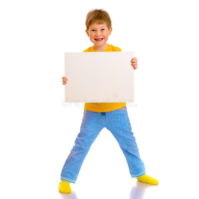 Een kleine jongen kijkt van achter een lege banner royalty-vrije stock foto