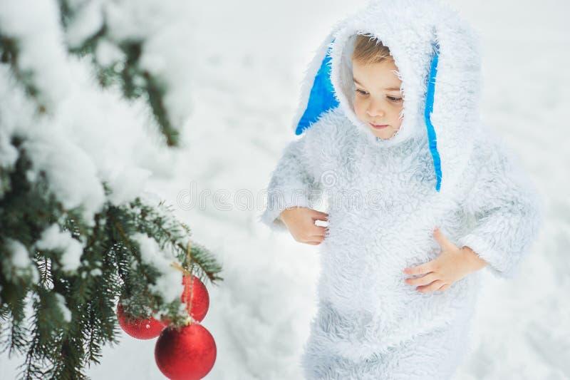 een klein jongetje verkleed als konijn en nieuw jaar stock fotografie