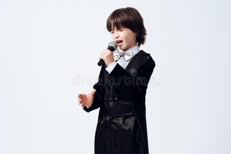 Een kleine jongen leert beroep van een zanger De donker-haired jongen in kostuum zingt in de microfoon stock foto's