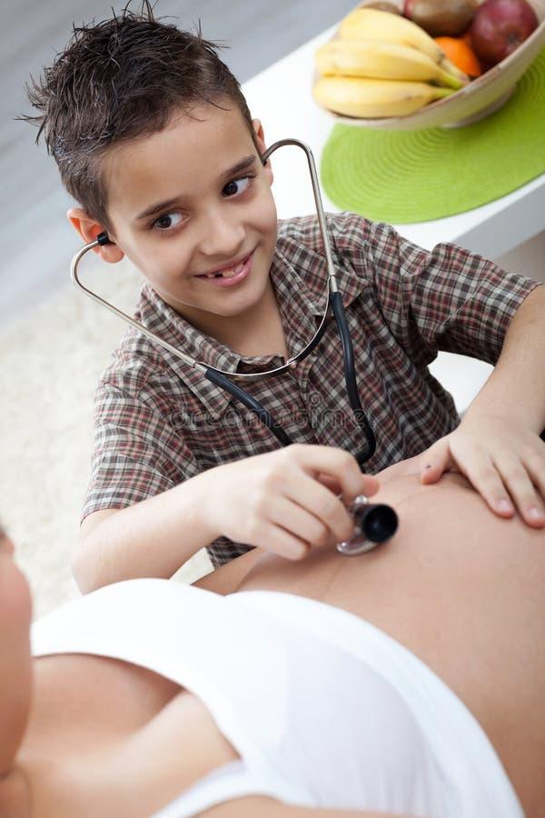 Een kleine jongen luistert aan een stethoscoopbuik van zijn zwanger mamma royalty-vrije stock afbeeldingen