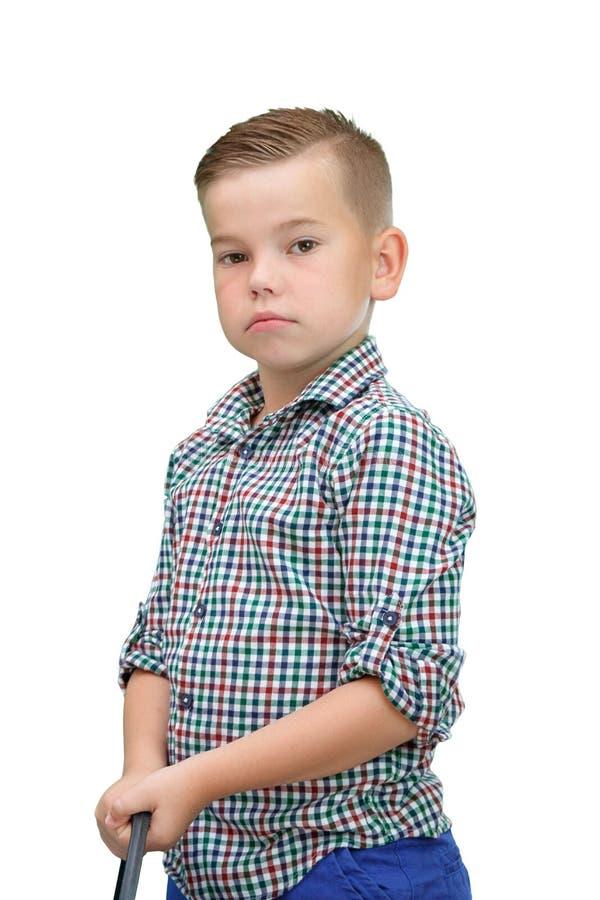 Een kleine jongen in een plaidoverhemd op een wit isoleerde achtergrondtribunes met een ZWABBER in zijn handen stock foto
