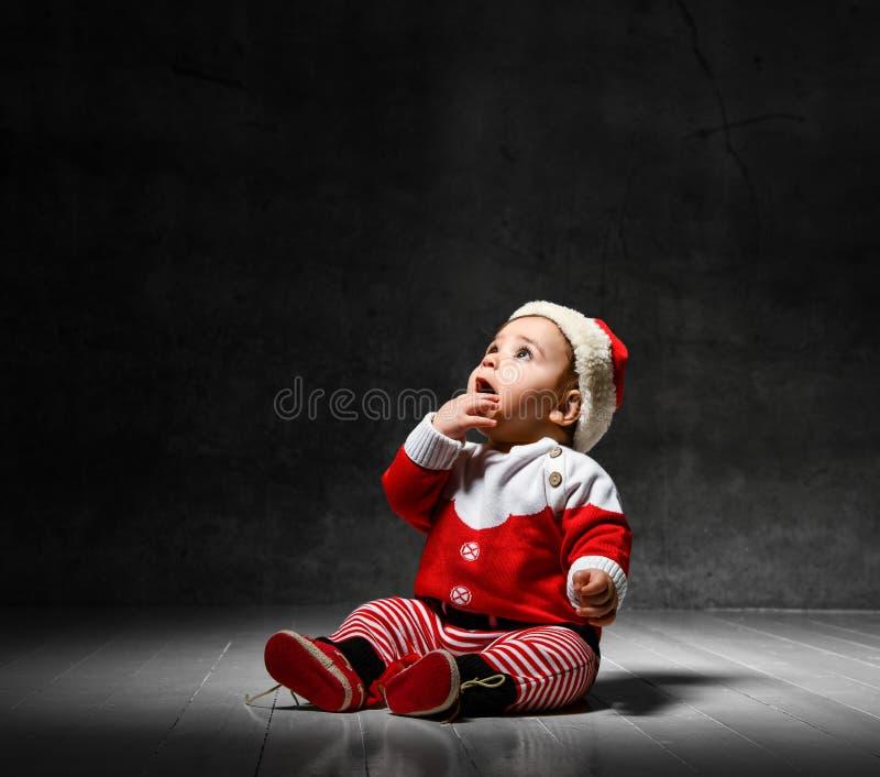 Een kleine kleine jongen in een rood sweater en een kerstpet, die op een donkere achtergrond zit stock foto
