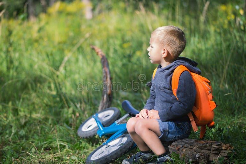Een kleine jongen rust op een logboek na het lopen royalty-vrije stock afbeelding
