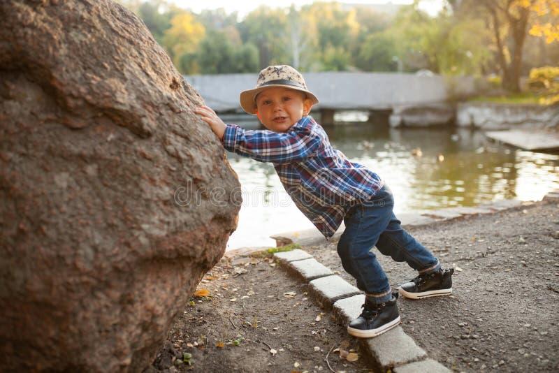 Een kleine jongen speelt en duwt een rots tijdens een gang in stock afbeelding
