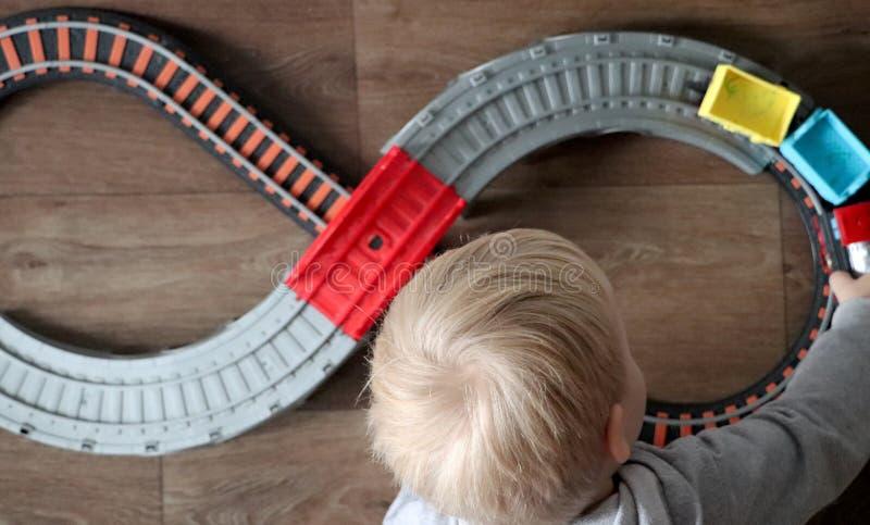 Een kleine jongen speelt een spoorweg van kinderen Het mamma let hierboven op haar zoon van Het kind wordt gefascineerd door de t stock afbeelding