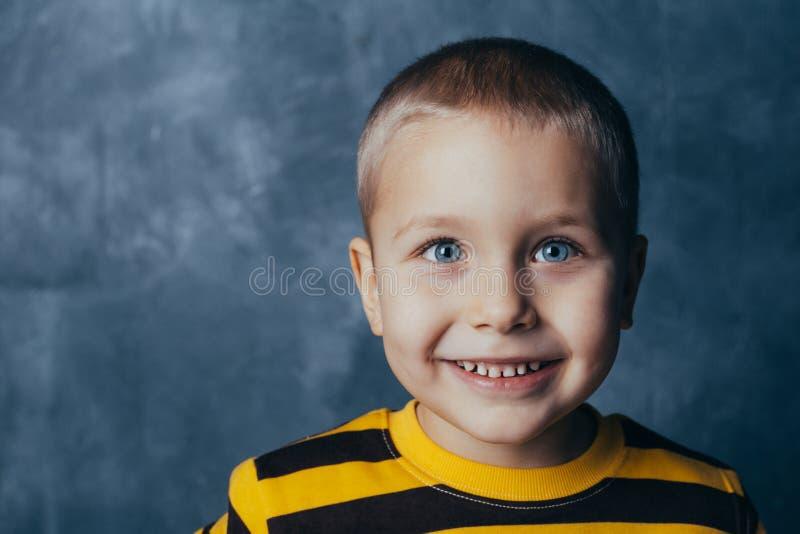 Een kleine jongen stelt voor een grijs-blauwe concrete muur Portret van een glimlachend kind gekleed in zwarte en gele gestreept royalty-vrije stock foto