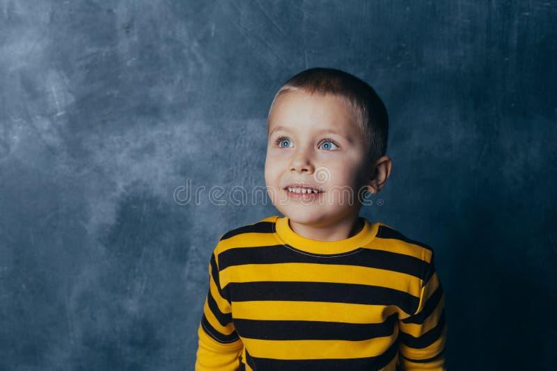 Een kleine jongen stelt voor een grijs-blauwe concrete muur Portret van een glimlachend kind gekleed in zwarte en gele gestreept stock foto