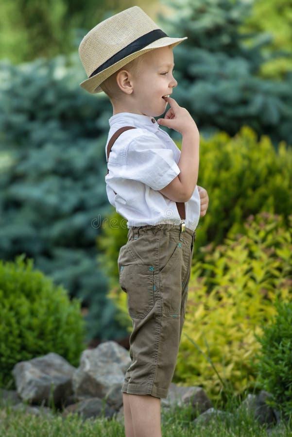 Een kleine jongen in een strohoed loopt in het Park Kleine, schuwe jongen stock foto's