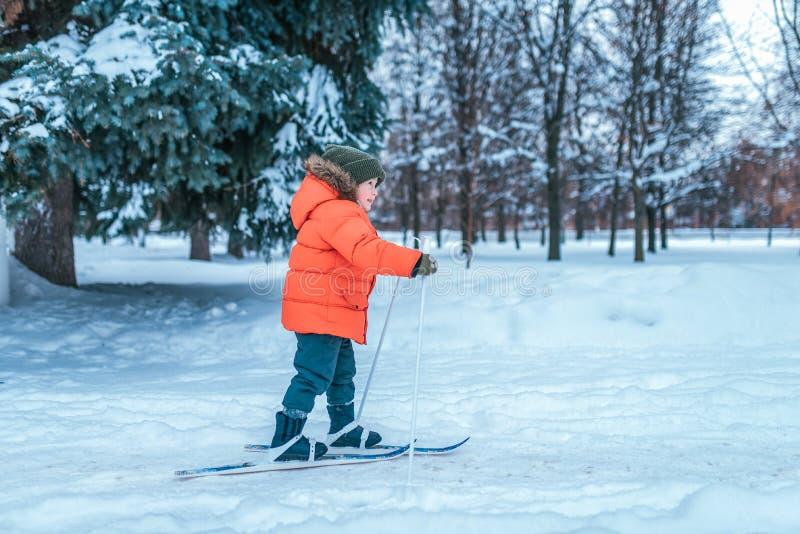 Een kleine jongen van 3-5 jaar oud berijdt één van het stuk speelgoed van kinderen skis De winter bosafwijkingen en houten afwijk royalty-vrije stock afbeeldingen