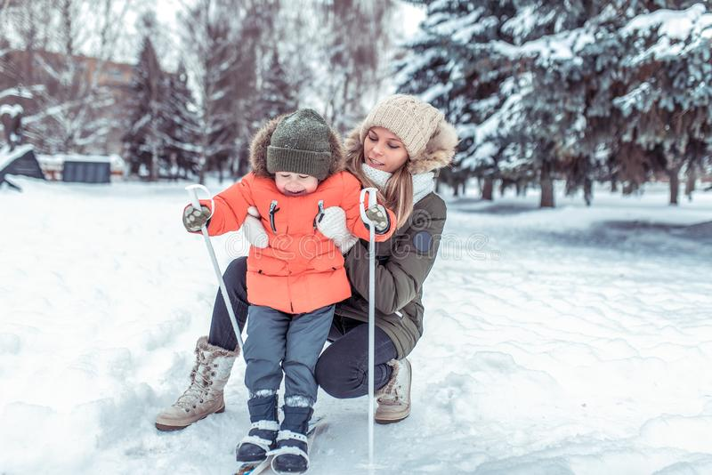Een kleine jongen van 3-5 jaar oud, staat op skis voor eerste keer op, in de winter in sneeuw bosa houdt een jonge moeder a stock fotografie